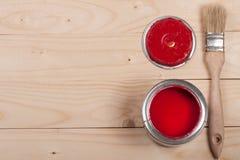 Pintura vermelha no banco a reparar e escovar no fundo de madeira claro com espaço da cópia para seu texto Vista superior foto de stock