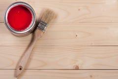 Pintura vermelha no banco a reparar e escovar no fundo de madeira claro com espaço da cópia para seu texto Vista superior fotografia de stock