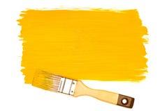 Pintura y cepillo amarillos Imagen de archivo