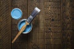 Pintura y cepillo azules en la madera imagenes de archivo