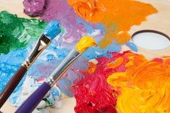 Pintura y cepillos coloreados de aceite en la paleta Fotografía de archivo