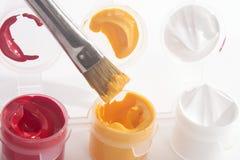 Pinturas acrílicas e pincel brancos amarelos vermelhos Fotografia de Stock Royalty Free