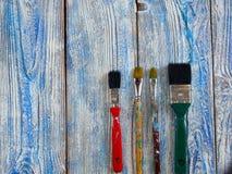 Pinturas acrílicas y cepillos coloreados en un fondo auténtico de hecho a mano con el copyspace Imagen de archivo