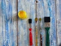 Pinturas acrílicas y cepillos coloreados en un fondo auténtico de hecho a mano con el copyspace Foto de archivo
