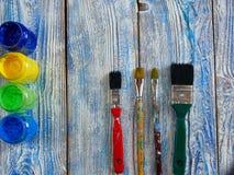 Pinturas acrílicas y cepillos coloreados en un fondo auténtico de hecho a mano con el copyspace Fotografía de archivo libre de regalías