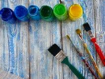 Pinturas acrílicas y cepillos coloreados en un fondo auténtico de hecho a mano con el copyspace Imagen de archivo libre de regalías