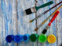 Pinturas acrílicas y cepillos coloreados en un fondo auténtico de hecho a mano con el copyspace Foto de archivo libre de regalías