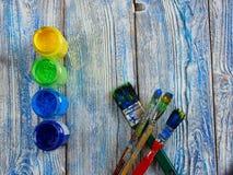 Pinturas acrílicas y cepillos coloreados en un fondo auténtico de hecho a mano con el copyspace Imágenes de archivo libres de regalías