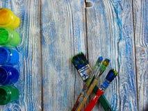 Pinturas acrílicas y cepillos coloreados en un fondo auténtico de hecho a mano con el copyspace Fotos de archivo libres de regalías