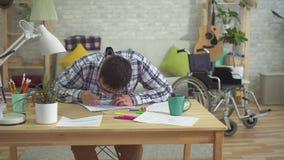 Pinturas autísticas masculinas adultas en la tabla en casa almacen de video