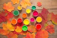 Pinturas, cepillos, hojas de otoño en fondo de madera Imagen de archivo