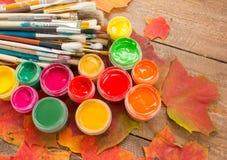 Pinturas, cepillos, hojas de otoño en fondo de madera Imágenes de archivo libres de regalías