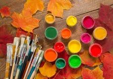 Pinturas, cepillos, hojas de otoño en fondo de madera Fotografía de archivo libre de regalías