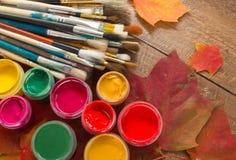Pinturas, cepillos, hojas de otoño en fondo de madera Imagen de archivo libre de regalías