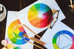 Pinturas, cepillos, lápices, dibujos y vidrios en la tabla de madera oscura Imagen de archivo libre de regalías