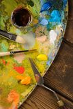 Pinturas, cepillos, paleta en un fondo de madera oscuro imagenes de archivo