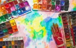 Pinturas, cepillos y paleta de la acuarela en el fondo colorido Imagen de archivo libre de regalías