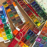 Pinturas, cepillos y paleta de la acuarela en fondo de madera Fotografía de archivo libre de regalías