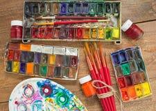 Pinturas, cepillos y paleta de la acuarela en fondo de madera Fotos de archivo libres de regalías