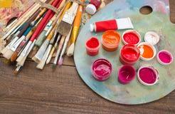 Pinturas, cepillos y paleta en el fondo de madera Fotos de archivo