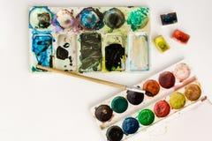 Pinturas coloridas brillantes de la acuarela con los cepillos y paleta en un fondo blanco Bandeja de la acuarela del primer Conce fotos de archivo