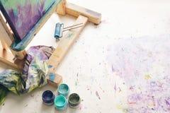 Pinturas com escova de pintura e lona na armação, vista superior imagem de stock royalty free