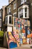 Pinturas com os retratos coloridos dos povos exibidos na rua Fotografia de Stock
