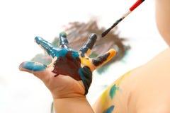 Pinturas da criança com pintura sua mão Fotografia de Stock