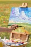 Pinturas da mão do artista com a escova na natureza Imagem de Stock