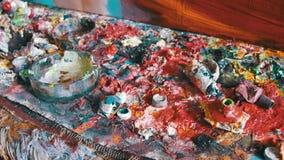 Pinturas de aceite multicoloras en el escritorio del ` s del artista en la galería de imágenes almacen de metraje de vídeo