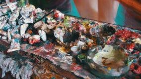 Pinturas de aceite multicoloras en el escritorio del ` s del artista en la galería de imágenes metrajes