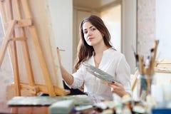 Pinturas de cabelos compridos da jovem mulher na lona Imagem de Stock Royalty Free