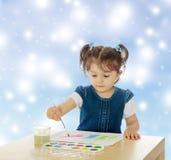 Pinturas de la niña con las acuarelas en la tabla Foto de archivo