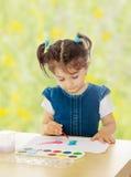 Pinturas de la niña con las acuarelas en la tabla Foto de archivo libre de regalías