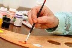 Pinturas de mistura da mão de uma mulher na paleta Fotografia de Stock Royalty Free
