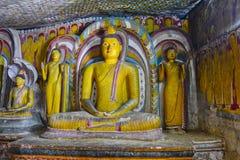 Pinturas de pared y estatuas de Buda en el templo de oro de la cueva de Dambulla Foto de archivo libre de regalías