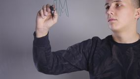 Pinturas de un hombre joven en el whiteboard de cristal almacen de video