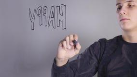 Pinturas de un hombre joven en el whiteboard de cristal metrajes