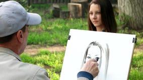 Pinturas del artista en el retrato de la lona de una chica joven, artista de la calle que trabaja en un parque de la ciudad almacen de video