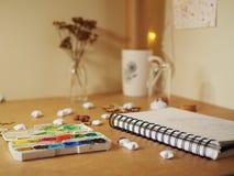 Pinturas del cuaderno y del watercolour en un escritorio foto de archivo libre de regalías