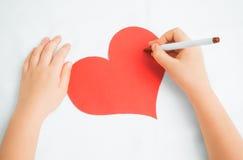 Pinturas del niño en un corazón de papel Foto de archivo libre de regalías