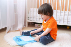 Pinturas del pequeño niño en la tableta magnética en casa Imagen de archivo