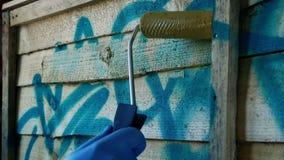 Pinturas do homem sobre grafittis na cerca With Roller video estoque