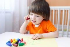 Pinturas do rapaz pequeno com lápis da cera Imagens de Stock Royalty Free