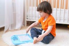 Pinturas do rapaz pequeno na tabuleta magnética Foto de Stock