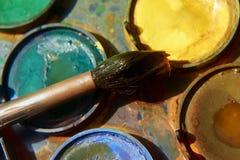 Pinturas e equipamento criançola da pintura, aquarelas e escovas, pinturas da cor de água Fotografia de Stock