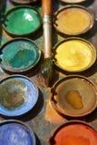 Pinturas e equipamento criançola da pintura, aquarelas e escovas, pinturas da cor de água Imagem de Stock Royalty Free