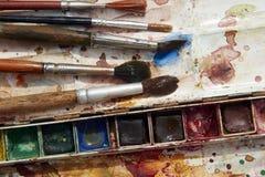 Pinturas e equipamento criançola da pintura, aquarelas e escovas, pinturas da cor de água Fotos de Stock