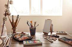 Pinturas e ferramentas na tabela de madeira na oficina do artista imagem de stock royalty free