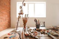 Pinturas e ferramentas na tabela de madeira na oficina do artista imagens de stock